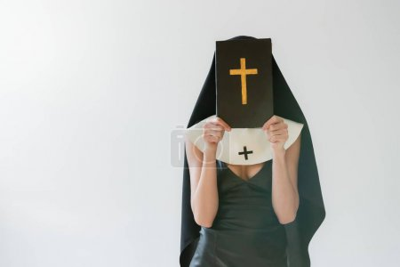Photo for Nun in sexy dress obscuring face with holy bible isolated on grey - Royalty Free Image