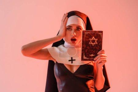Photo pour Choquée nonne en robe sexy touchant la tête tout en tenant bible juive isolé sur rose - image libre de droit