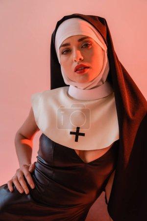 Photo pour Nonne sensuelle en robe sexy regardant la caméra isolée sur rose - image libre de droit