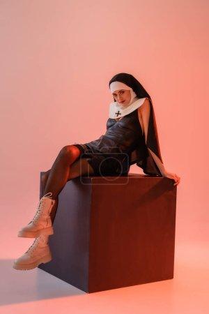 Photo pour Jeune nonne en robe sexy et bottes blanches assis sur cube noir sur fond rose - image libre de droit