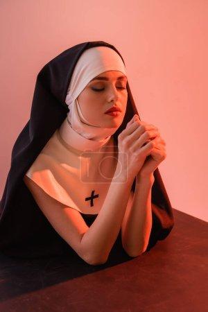 Photo pour Jeune religieuse priant les yeux fermés sur une surface noire isolée sur du rose - image libre de droit