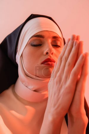 Photo for Young nun praying with closed eyes isolated on pink - Royalty Free Image