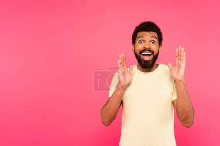 amazed african american man gesturing isolated on pink