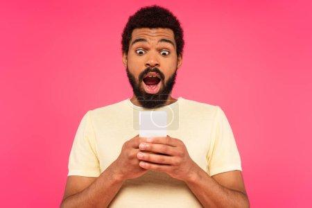 sorprendido hombre afroamericano utilizando teléfono inteligente aislado en rosa