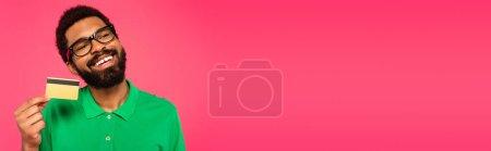 Photo pour Heureux homme afro-américain dans des lunettes tenant la carte de crédit isolé sur rose, bannière - image libre de droit