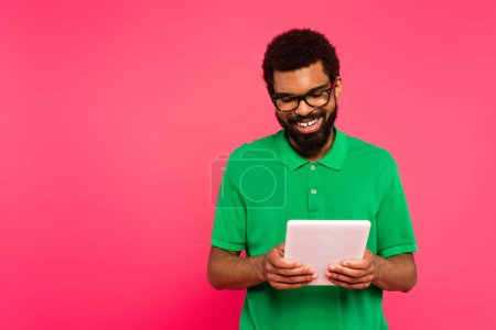happy african american man in glasses and green polo shirt using digital tablet isolated on pink