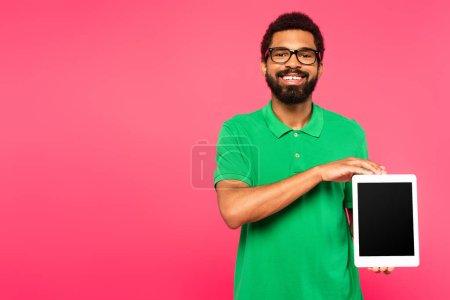 Photo pour Heureux homme afro-américain dans des lunettes tenant tablette numérique avec écran vide isolé sur rose - image libre de droit
