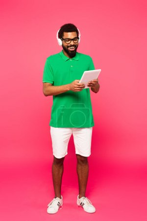 full length of cheerful african american man in glasses and headphones using digital tablet on pink