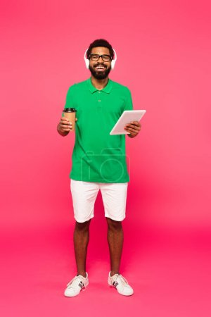 full length of cheerful african american man in glasses and headphones holding paper cup and digital tablet on pink