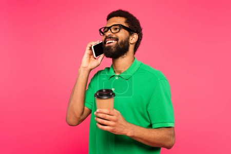 african american man in glasses and green polo shirt talking on smartphone while holding paper cup isolated on pink