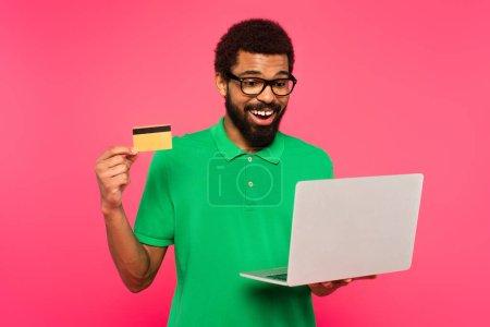 Photo pour Heureux homme afro-américain dans des lunettes et un polo vert tenant ordinateur portable et carte de crédit isolé sur rose - image libre de droit