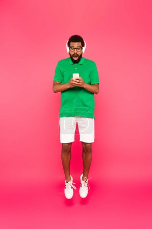 Photo for Full length of surprised african american man in glasses and headphones using smartphone on pink - Royalty Free Image