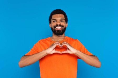 Photo pour Heureux et barbu homme afro-américain montrant signe du cœur avec les mains isolées sur bleu - image libre de droit