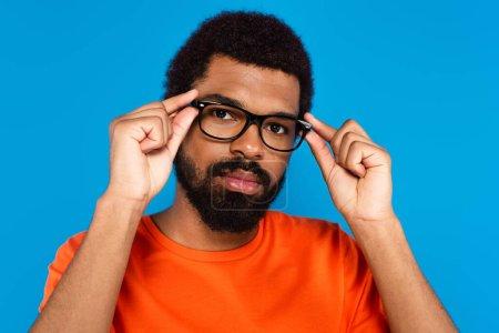 bärtiger afrikanisch-amerikanischer Mann justiert Brille isoliert auf blau