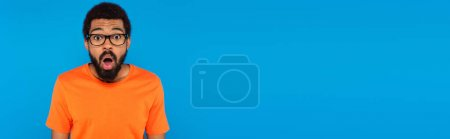 Photo for Shocked african american man in glasses isolated on blue, banner - Royalty Free Image