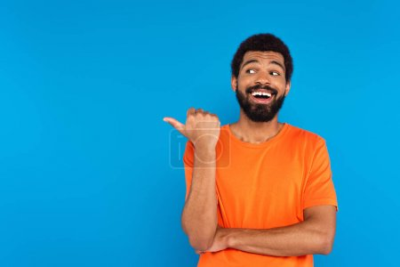 Photo for Happy african american man in glasses pointing with thumb isolated on blue - Royalty Free Image