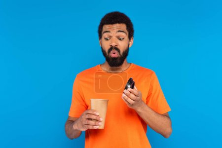 Photo for Surprised african american man looking at coffee to go in paper cup isolated on blue - Royalty Free Image