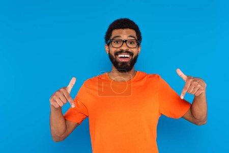 glücklich afrikanisch-amerikanischer Mann zeigt mit Fingern isoliert auf blau