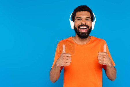 joyful african american man in wireless headphones listening music while showing thumbs up isolated on blue