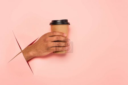 partial view of african american man holding paper cup on ripped pink background