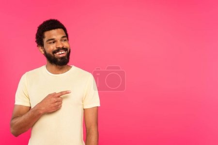 cheerful and bearded african american man smiling while pointing with finger isolated on pink