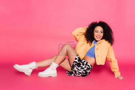 full length of happy african american woman in crop top, jacket and skirt with animal print sitting on pink