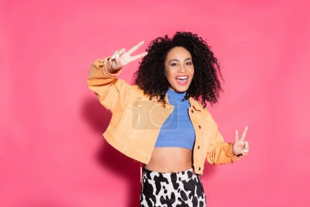 happy african american woman in crop top, jacket and skirt with animal print showing peace sign on pink