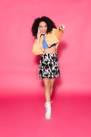 Photo pour Pleine longueur de femme afro-américaine heureuse en haut de culture et veste parler sur smartphone tout en pointant du doigt sur rose - image libre de droit