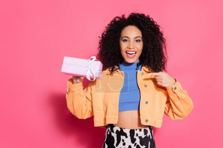 amazed african american woman in crop top and jacket pointing at present on pink