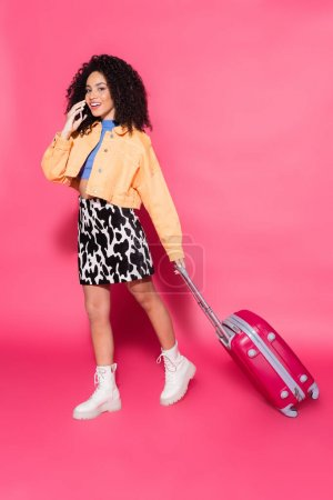 full length of cheerful african american woman talking on smartphone and walking with suitcase on pink