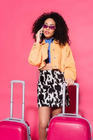african american woman in sunglasses talking on smartphone near suitcases on pink
