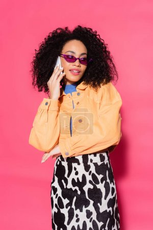 curly african american woman in sunglasses talking on smartphone on pink