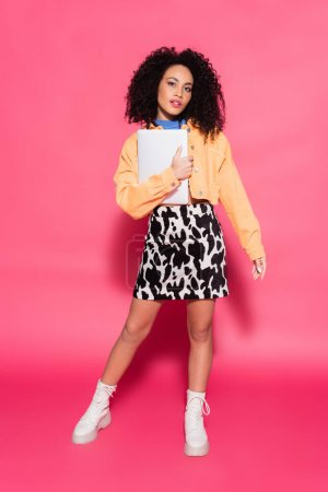 full length of curly african american woman posing with laptop on pink