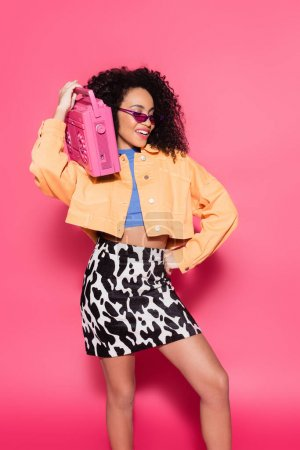 happy african american woman in sunglasses holding boombox and posing with hand on hip on pink