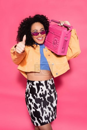 happy african american woman in sunglasses holding boombox and showing thumb up on pink