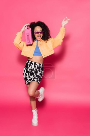 full length of happy african american woman in sunglasses holding boombox and posing on pink