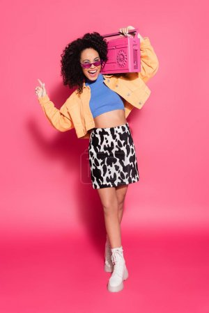 full length of cheerful african american woman in sunglasses holding boombox and posing on pink