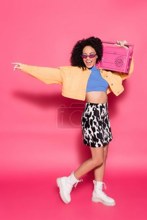 full length of positive african american woman in sunglasses holding boombox and posing on pink