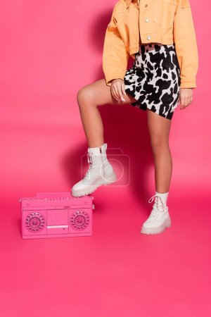 cropped view of african american woman in skirt with animal print standing near retro boombox on pink