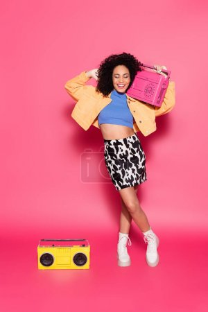 Photo for Full length of african american woman posing with boombox on pink - Royalty Free Image