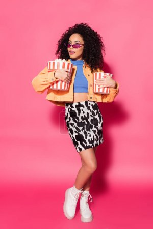 full length of african american woman in sunglasses holding buckets of popcorn on pink