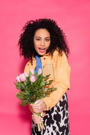 mujer americana africana rizada asombrada sosteniendo ramo de flores en rosa