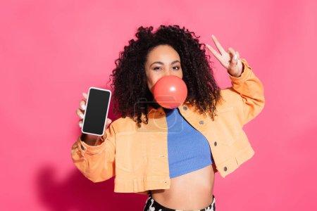 Photo pour Femme afro-américaine bouclée soufflant chewing-gum, montrant signe de paix et tenant smartphone avec écran blanc sur rose - image libre de droit
