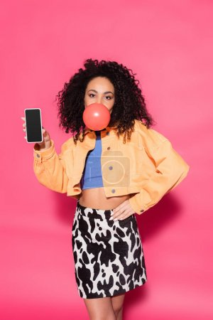 curly african american woman blowing bubble gum and holding smartphone with blank screen on pink
