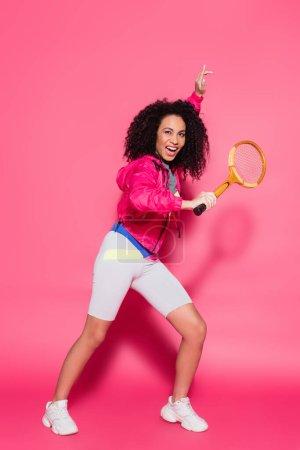 Photo pour Pleine longueur de femme africaine américaine étonnante et sportive tenant une raquette de tennis sur rose - image libre de droit