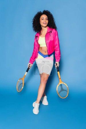 Photo pour Pleine longueur de joyeux jeune femme afro-américaine tenant des raquettes de tennis sur bleu - image libre de droit