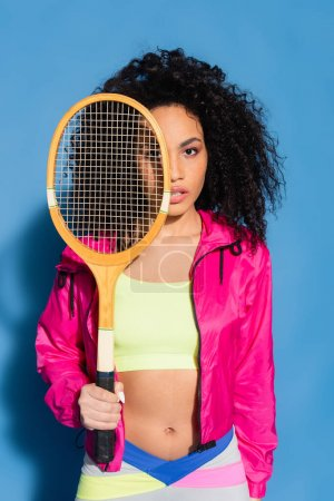 young african american woman posing with tennis racket and looking at camera on blue
