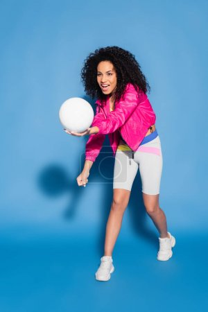 full length of amazed african american woman in pink jacket playing volleyball on blue