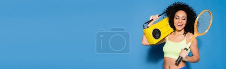 happy african american woman holding boombox and tennis racket on blue, banner
