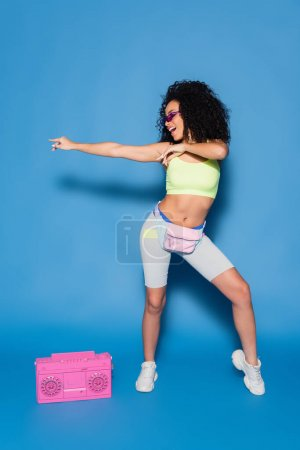 full length of happy african american woman in sunglasses and waist bag pointing near pink boombox on blue
